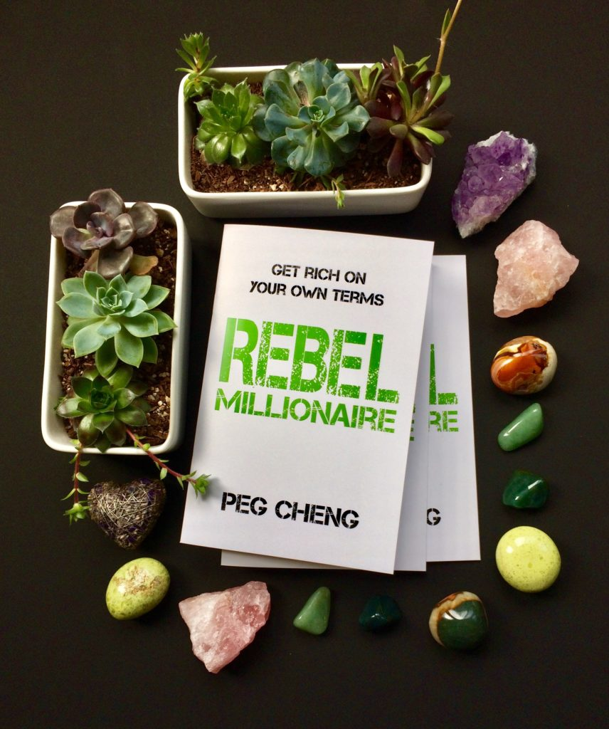Rebel Millionaire by Peg Cheng surrounded by crystals and succulents